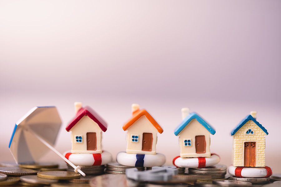 home insurance concept, house models on lifeboats with coins representing home insurance policies