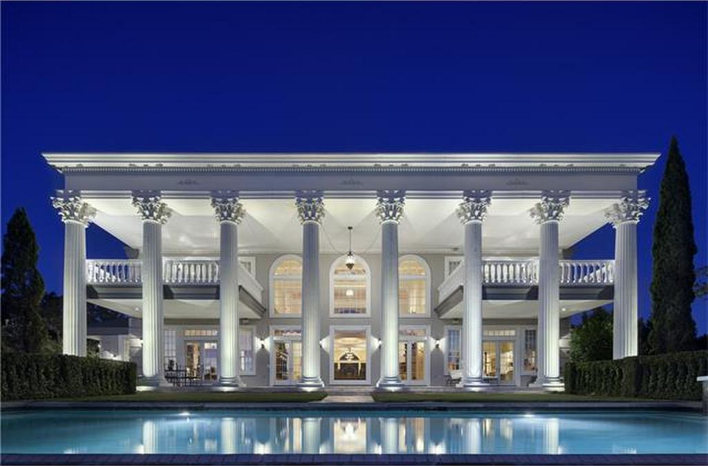 front elevation of austin mansion with white pillars and reflecting pool